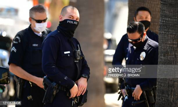 "Los Angeles Police Department officers wear facial covering while monitoring an ""Open California"" rally in downtown Los Angeles, on April 22, 2020. -..."