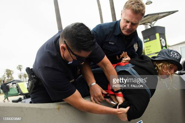 Los Angeles Police Department offices wrestle a knife away from a person experiencing homelessness as they were detained during an event with Los...