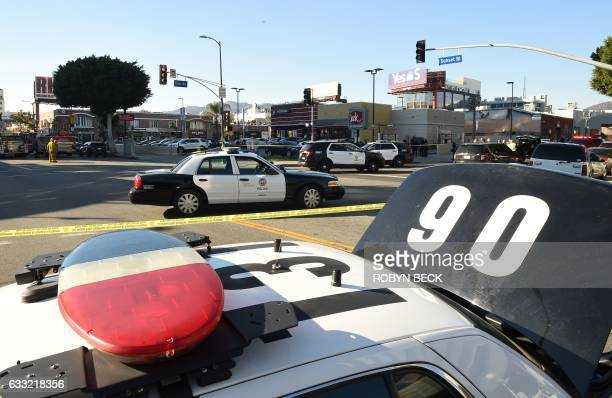 Los Angeles Police Department police cars fill the intersection outside a Jack in the Box restaurant in Hollywood California January 31 after police...