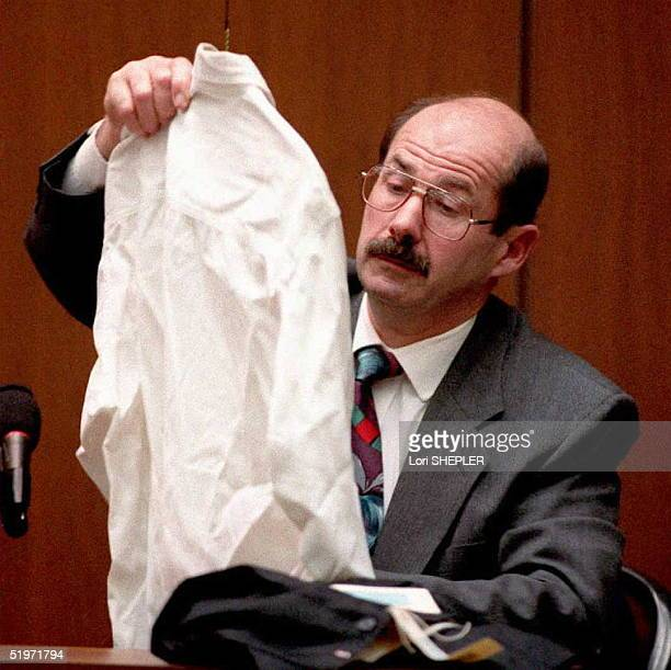 Los Angeles Police Detective Tom Lange one of the lead investigators in the OJ Simpson murder case examines a shirt 06 March of murder victim Ronald...