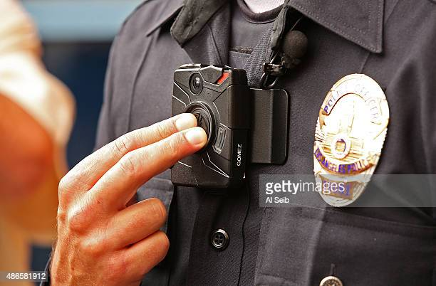 Los Angeles Police Officer Jim Stover, with Information Technology Bureau demonstrates how an officer turns on the new LAPD body camera during a...