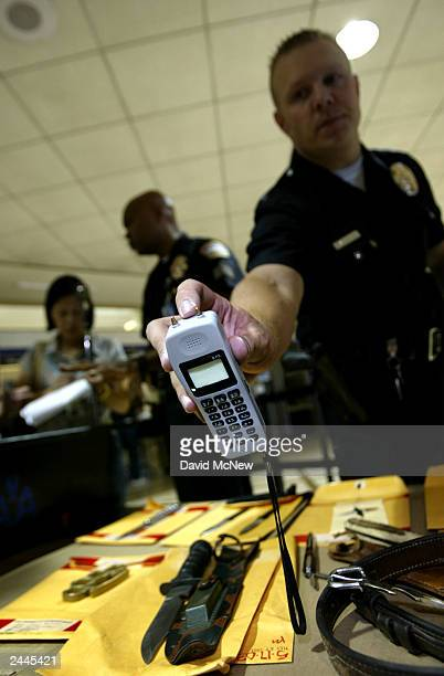 Los Angeles Police officer Joel Sydanman holds a taser stun gun shaped like a cell phone that was confiscated from a passenger August 29 2003 in Los...