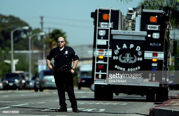 Los Angeles Police Officer stands near the Bomb Squad unit as LAPD and ATF agents investigate the scene where a Lincoln Navigator was vandalized and...