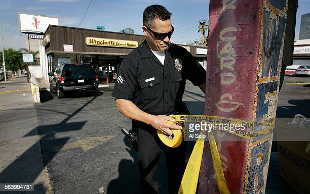 HOMICIDES Los Angeles police officer Vic Gutierrez uses crime scene tape to contain the scene of a homocide in the Westlake/Koreatown area From Jill...