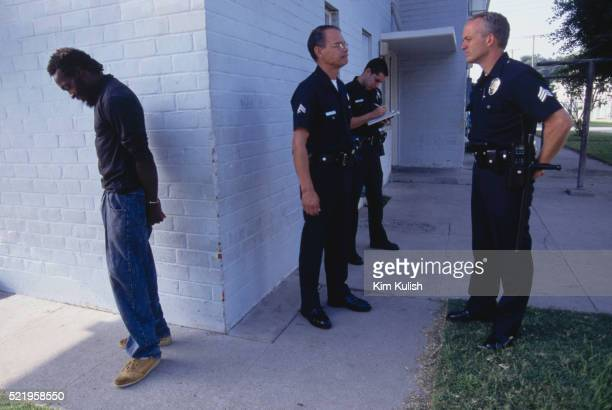 los angeles police officers detaining a suspect - los angeles police department stock pictures, royalty-free photos & images