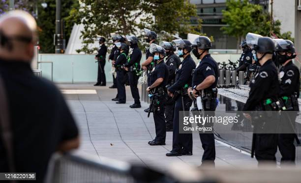 Los Angeles Police officers in riot gear and face masks stand on the other side of metal fence barriers in front of headquarters to keep Black Lives...