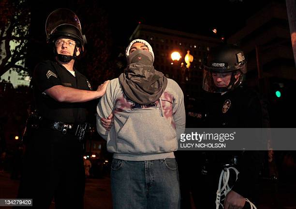 Los Angeles police officers search a protester arrested from the Occupy Los Angeles encampment outside City Hall on November 30 2011 Riot police...