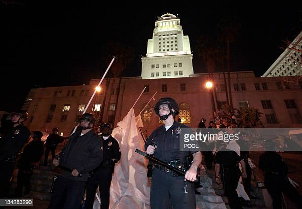 Los Angeles police officers stand guard as they evict protesters from the Occupy LA encampment outside City Hall in Los Angeles November 30 2011 The...