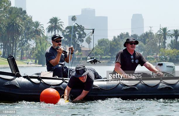 Los Angeles Police Underwater Dive Unit members Dave Mascaranas Kelly Kocure and Jim Moody prepare to use a remote underwater camera to search for...