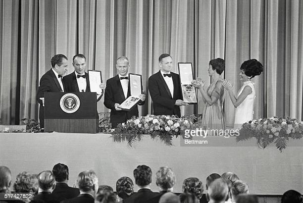 President Nixon presents Apollo 11 astronauts with the Freedom Award as two of their wives Mrs Armstrong and Mrs Collins applaud The astronauts...