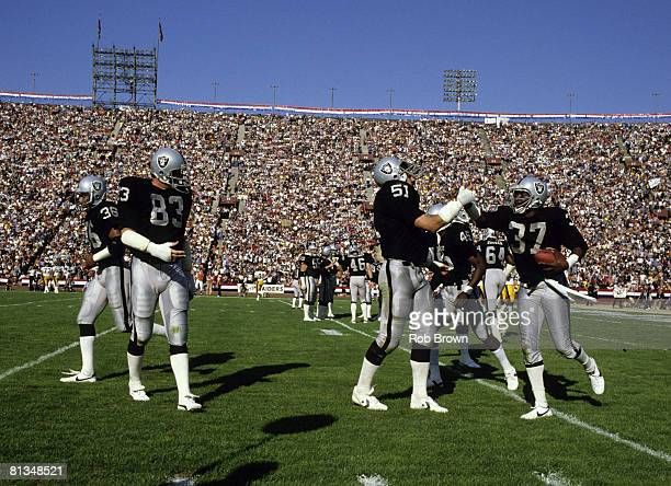 Los Angeles Raiders cornerback Lester Hayes is congratulated by his teammates as he comes off the field following his 18yard interception return for...
