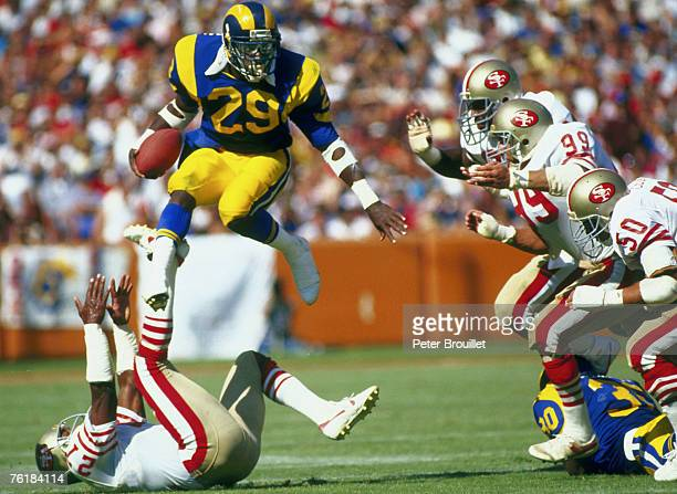 Los Angeles Rams Hall of Fame running back Eric Dickerson goes airborne to avoid the San Francisco 49ers defense in a game at Anaheim Stadium.