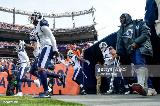 Los Angeles Rams players including wide receiver Robert Woods and cornerback Aqib Talib walk onto the field before a game against the Denver Broncos...