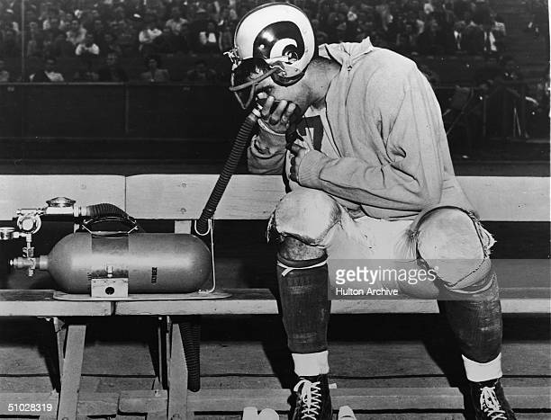 Los Angeles Rams quarterback Bob Waterfield inhales pure oxygen from a 'vitalator' respirator machineduring a pause in a football game September 25...