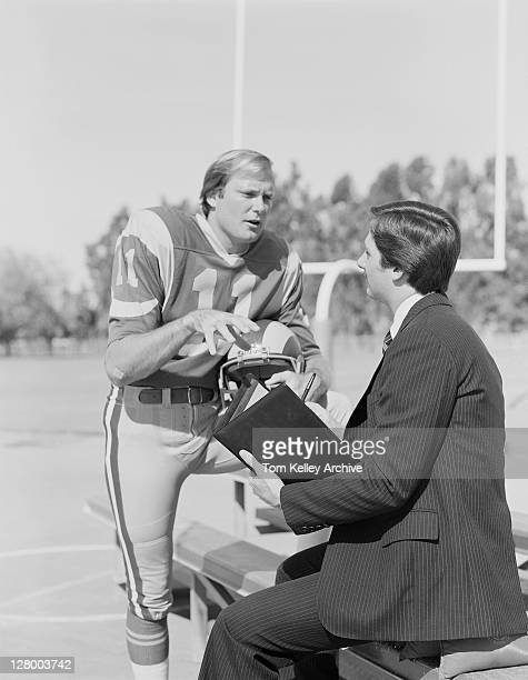 Los Angeles Rams quarterback Pat Haden talking to a man with a notebook on the training field 1979