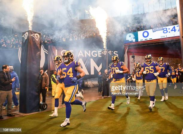 Los Angeles Rams run onto the field ahead of the NFC Divisional Round playoff game against the Dallas Cowboys at Los Angeles Memorial Coliseum on...