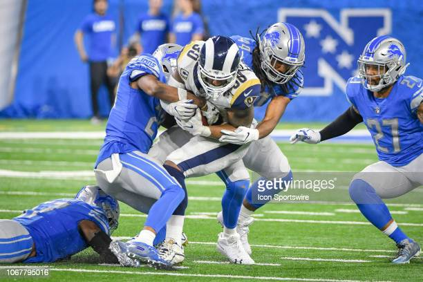 Los Angeles Rams running back Todd Gurley is gang tackled by Detroit Lions linebacker Jalen Reeves-Maybin and Detroit Lions strong safety Quandre...