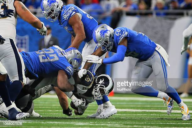 Los Angeles Rams running back Todd Gurley is taken down by Detroit Lions defensive end Da'Shawn Hand and Detroit Lions defensive back DeShawn Shead...