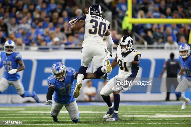 Los Angeles Rams running back Todd Gurley runs the ball under the pressure of Detroit Lions free safety Glover Quin during the first half of an NFL...