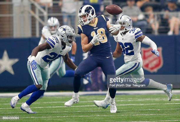 Los Angeles Rams wide receiver Cooper Kupp bobbles a reception in front of a hit from Dallas Cowboys safety Xavier Woods in the first half on Sunday,...