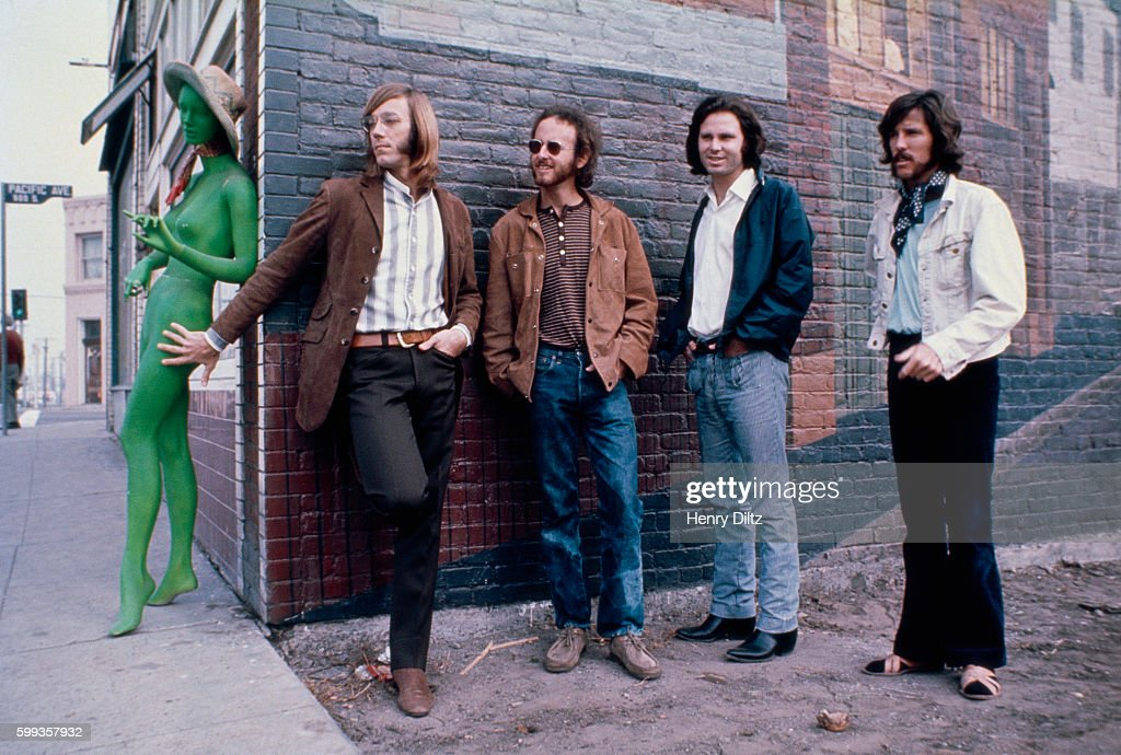 Los Angeles rock band The Doors stand alongside a brick building with an unclothed green mannequin. Left to right are: Ray Manzarek, keyboards; Robbie Krieger, guitar; Jim Morrison, vocals; John Densmore, drums.
