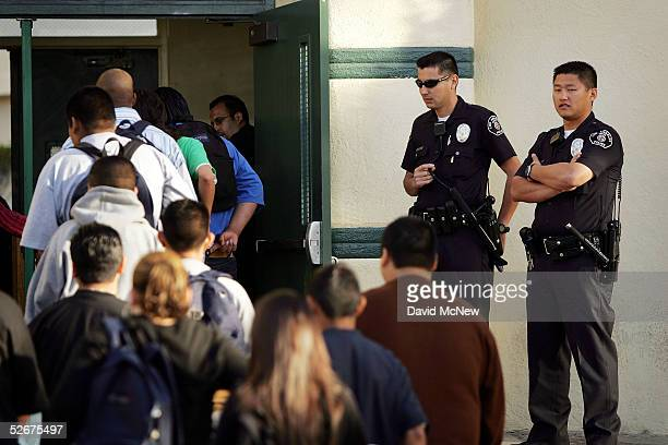 Los Angeles School Police officers watch students lining up to pass through a security check point in the aftermath of two apparent racially...