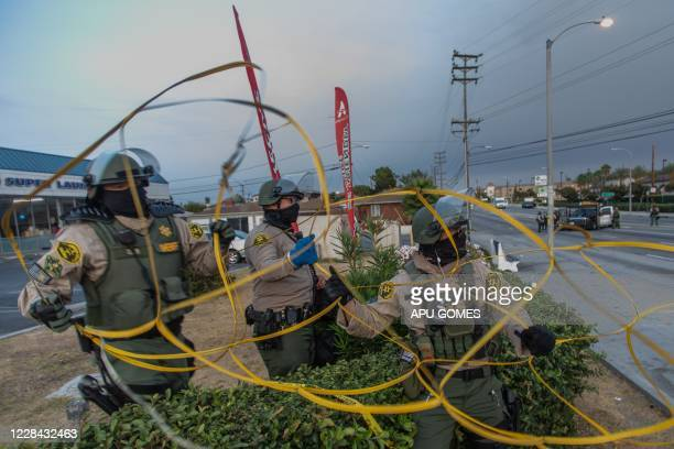 Los Angeles Sheriff's deputies set up a barrier to block Imperial Hwy at the intersection of Normandie Avenue in South Los Angeles to protect the...