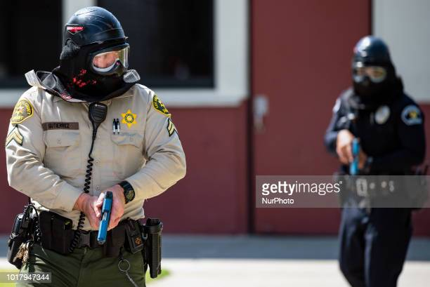 A Los Angeles Sheriffs deputy and a police officer participate in an active shooter drill in a high school near Los Angeles California on August 16...