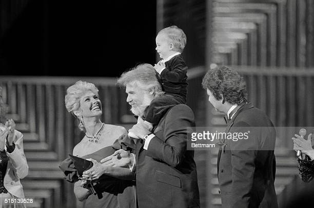 Singer Kenny Rogers acknowledges the cheers of the audience as he holds his 13 month old son Christopher Cody on his shoulders after Rogers received...