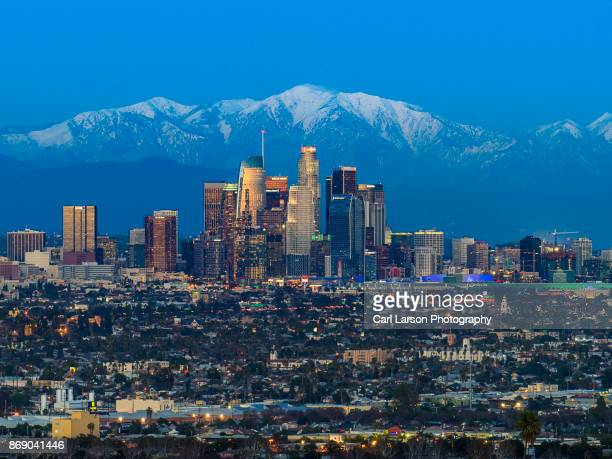 los angeles skyline with snow capped mountains - de stad los angeles stockfoto's en -beelden