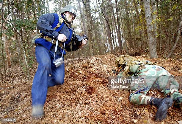 Los Angeles Times photographer Kevin Casey jumps for cover next to a US Army infantry soldier during media training exercises at the US Army Infantry...