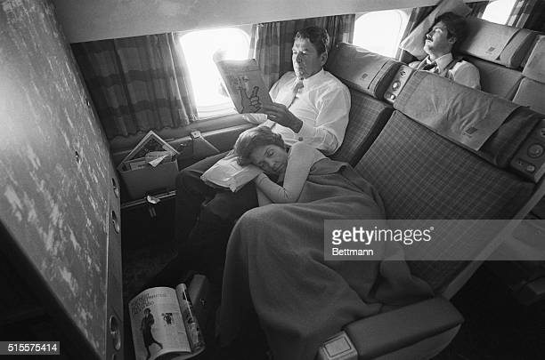 Tired campaigner Nancy Reagan catches '40 winks' on her husbands lap during flight returning them to California Aug 7 from a trip to the South and...