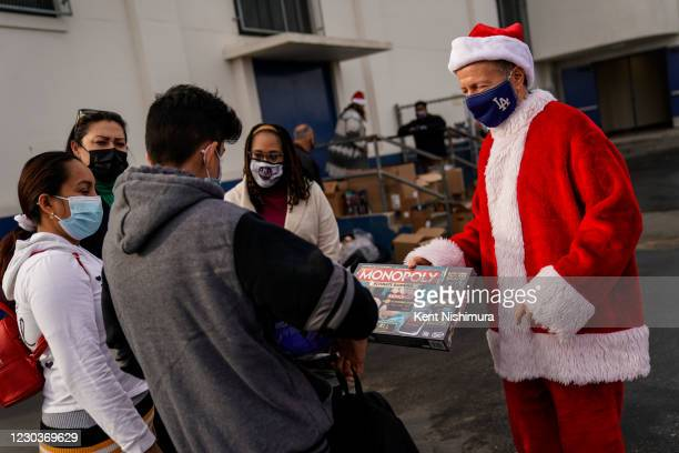 Los Angeles Unified School District Superintendent Austin Beutner, dressed as Santa Claus hands Yordin Hernandez a 9th grader at Washington Prep High...