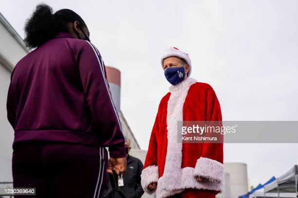 Los Angeles Unified School District Superintendent Austin Beutner, dressed as Santa Claus, talks with the Kaiya McKoy during an event at Washington...