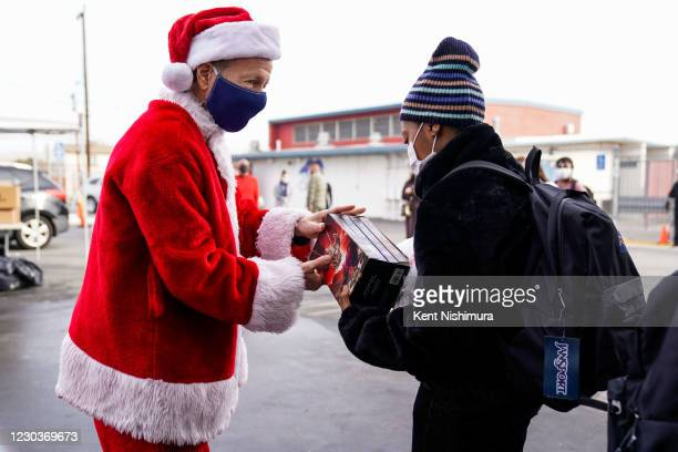 Los Angeles Unified School District Superintendent Austin Beutner, dressed as Santa Claus, gives a set of novels to Zamya Hayes during an event at...