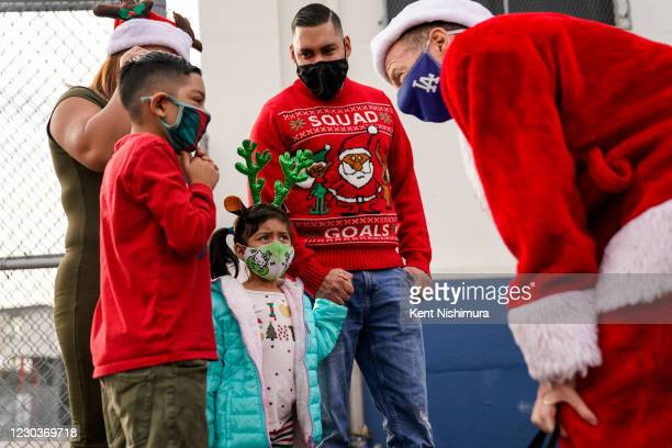Los Angeles Unified School District Superintendent Austin Beutner, dressed as Santa Claus, right, speaks with Anthony Giron, while his younger...