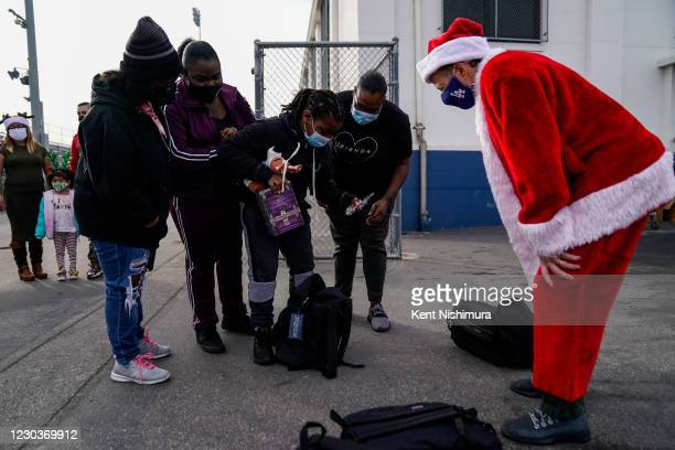 Los Angeles Unified School District Superintendent Austin Beutner, dressed as Santa Claus, talks with the Kayell McKoy Kaiya McKoy Kenric McKoy and...