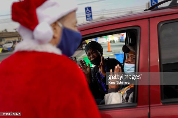 Los Angeles Unified School District Superintendent Austin Beutner, dressed as Santa Claus, gives out gifts and candy during an event at Washington...