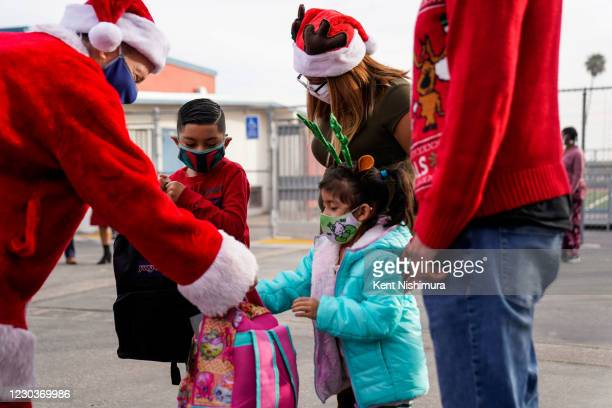 Los Angeles Unified School District Superintendent Austin Beutner, dressed as Santa Claus, hands gifts to Anthony Giron and his younger sister...