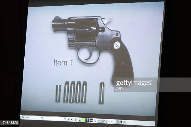 A photograph showing the gun that killed Lana Clarkson with the rounds of ammunition recovered from the cylinder of the gun is displayed on a screen...