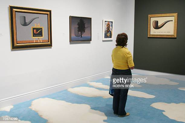 A visitors views some of the most famous works by Belgian surrealist Rene Magritte including 'Ceci N'est Pas Une Pipe' at the preview of 'Magritte...