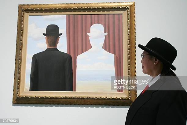 Gallery security guard J Dulay poses beside 'Decalcomania' by Belgian surrealist artist Rene Magritte at the preview of 'Magritte and Contemporary...