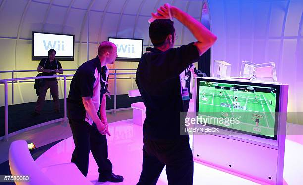 Nintendo game demonstrators play tennis with Nintendo's new Wii home console which lets users manipulate action on their television screens through...