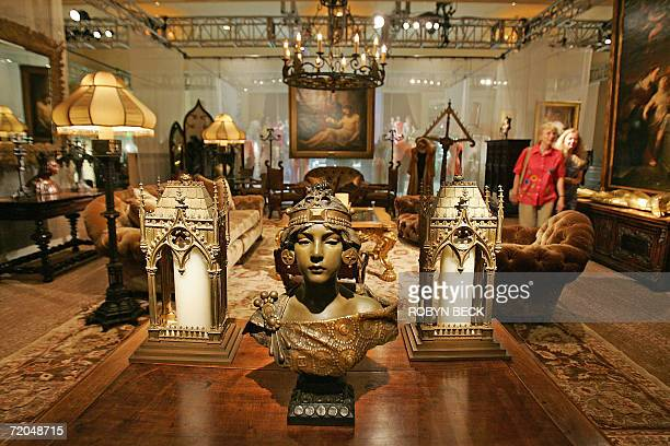 Los Angeles, UNITED STATES: Two visitors walk through a room of furnishing from the Malibu home of Cher, including in the foreground an art nouveau...