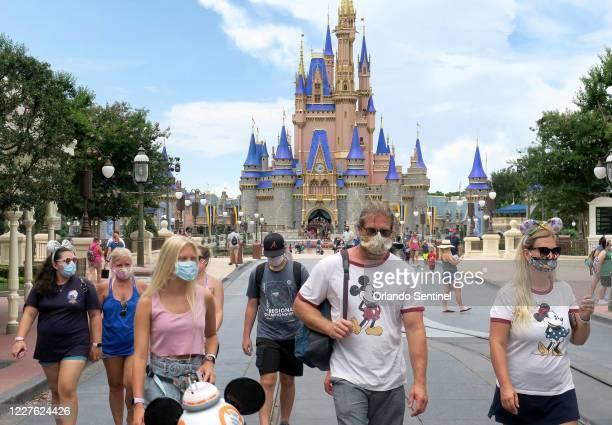 Los visitantes usan máscaras para asistir al día oficial de reapertura del Magic Kingdom en Walt Disney World en Lake Buena Vista, Florida, el sábado...