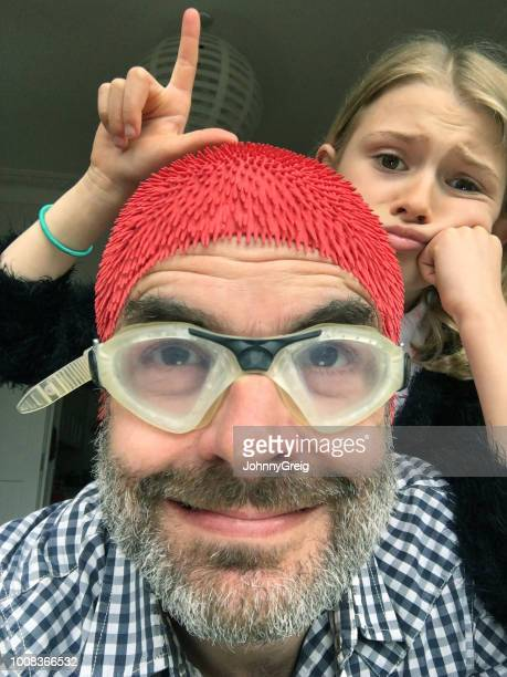 loser dad selfie - unimpressed photobomber daugther makes an l sign at father - naughty daughter stock photos and pictures