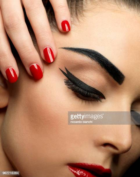 lose-up of woman with red lipstick red polish and black eyeliner - eye liner stock photos and pictures