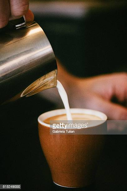 loseup shot of a milk being poured into the cup of cappuccino