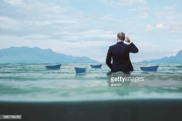 lost and confused businessman in water - falência imagens e fotografias de stock