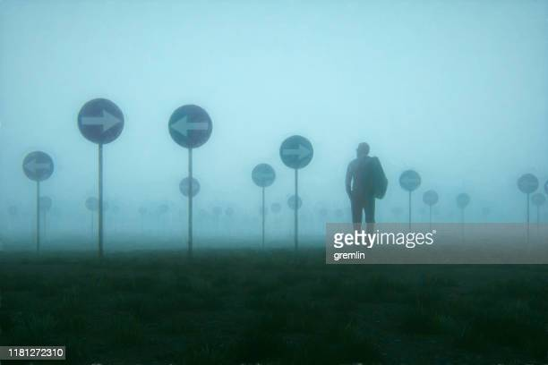 lost and confused businessman walking in meadow - uncertainty stock pictures, royalty-free photos & images